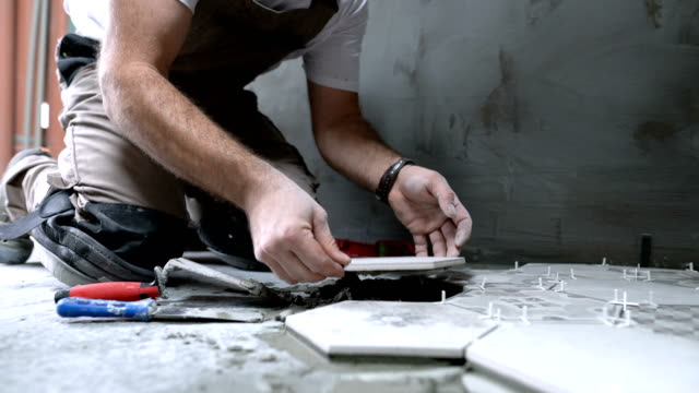 professional tiler laying tiles on the floor - bathroom stock videos & royalty-free footage