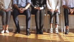 Professional unemployed business people sit on chairs, legs closeup view