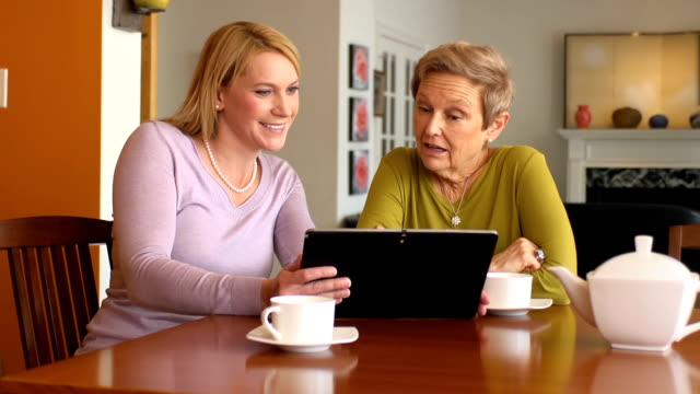 Professional Uses Digital Tablet with Senior Woman