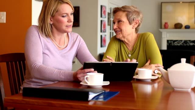 vídeos de stock, filmes e b-roll de profissional com tablet digital com a mulher idosa - testamento