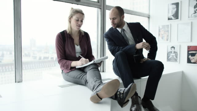 a professional woman making notes on a pad in a high rise office environment watched by a male colleague - legs crossed at ankle stock videos & royalty-free footage