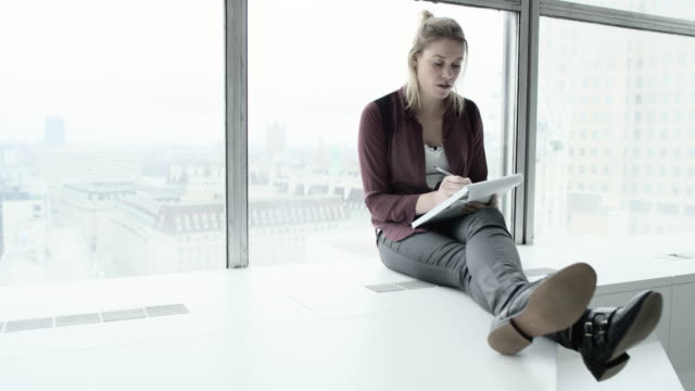 a professional woman making notes on a pad in a high rise office environment - legs crossed at ankle stock videos & royalty-free footage
