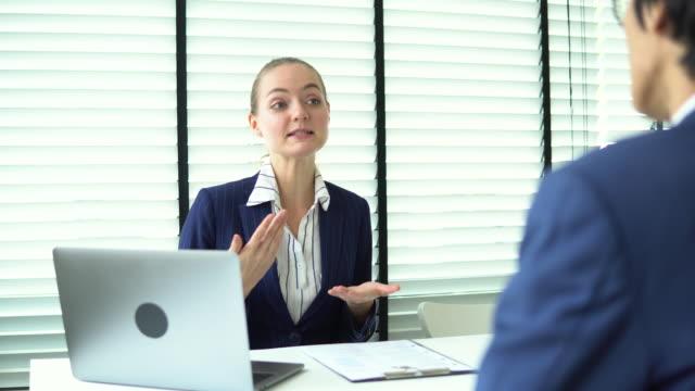 vidéos et rushes de réunion professionnelle de femme dans le bureau avec le jeune homme d'affaires - avocat juriste
