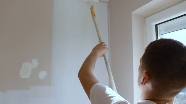 professional worker painting the wall in white color using a painting roller - renovation stock videos & royalty-free footage