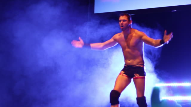 A Professional wrestler makes is entrance to the ring on a smokey light filled stage