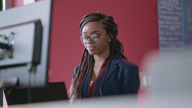 professional young african-american woman works at her desk, glancing at her computer monitors - satisfaction stock videos & royalty-free footage