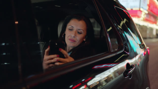 professionally dressed business woman takes photos of the neon lights of the las vegas strip out of her window in the backseat of a black suv - convention stock videos & royalty-free footage