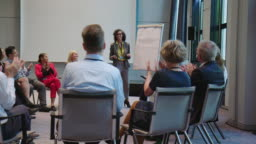 Professionals applauding for colleague in seminar