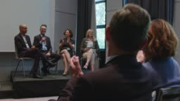 Professionals clapping for businessman at seminar