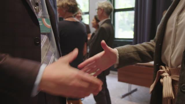 profis, die handshake bei konferenzveranstaltungen machen - berufliche partnerschaft stock-videos und b-roll-filmmaterial