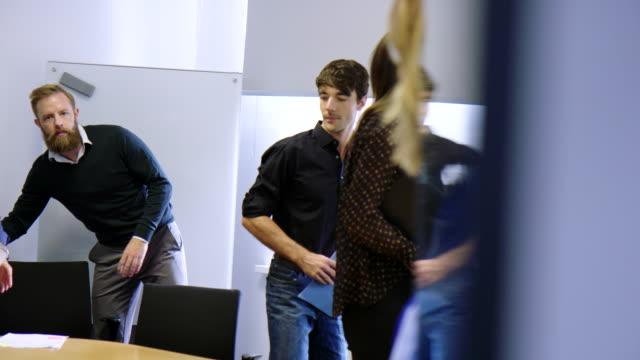 vídeos de stock e filmes b-roll de professionals leaving the boardroom after a meeting - acabado