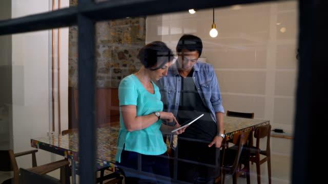 vídeos de stock, filmes e b-roll de professionals using digital tablet in board room - touch screen