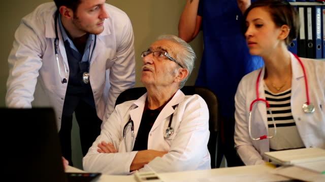 vidéos et rushes de professeur et assistant de médecins travaillant sur un ordinateur portable. - débat