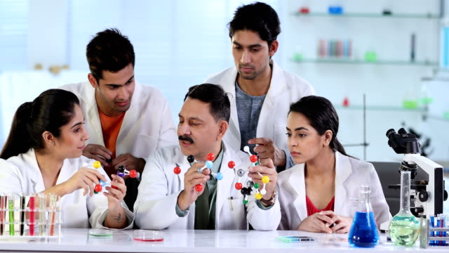 vídeos y material grabado en eventos de stock de ms professor explaining students about molecular structure in laboratory / delhi, india - camisa y corbata