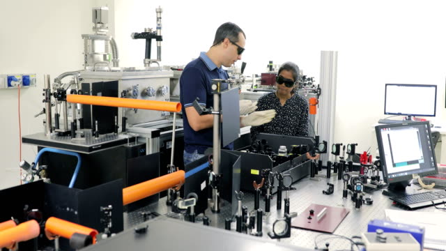 professor explaining to a student how to use powerful high frequency laser in laboratory - safety glasses stock videos & royalty-free footage