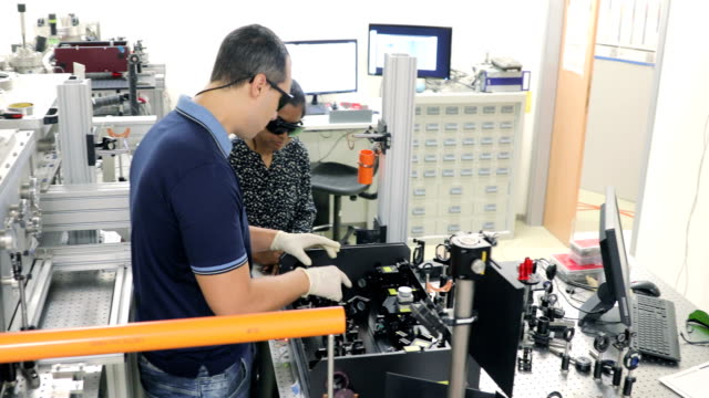 Professor Explaining to a Student How to Use Powerful High Frequency Laser in Laboratory