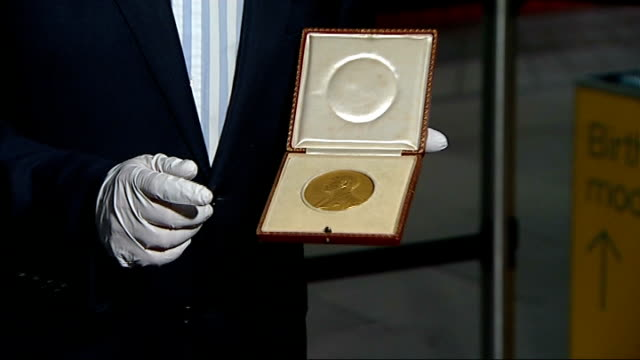 professor peter higgs awarded nobel prize for physics; england: london: science museum: int reporter to camera holding nobel medal - medal stock videos & royalty-free footage