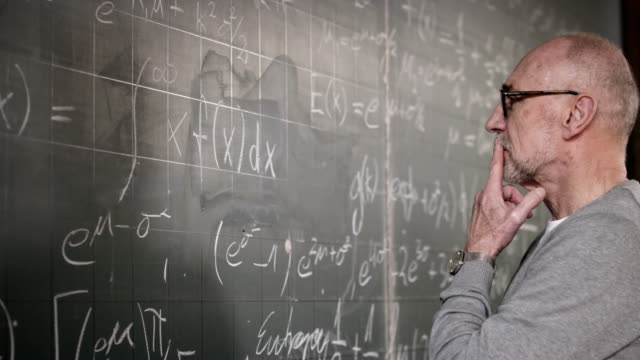 Professor writing on blackboard