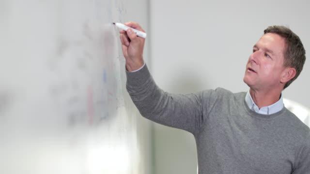 professor writing on whiteboard - whiteboard stock videos & royalty-free footage