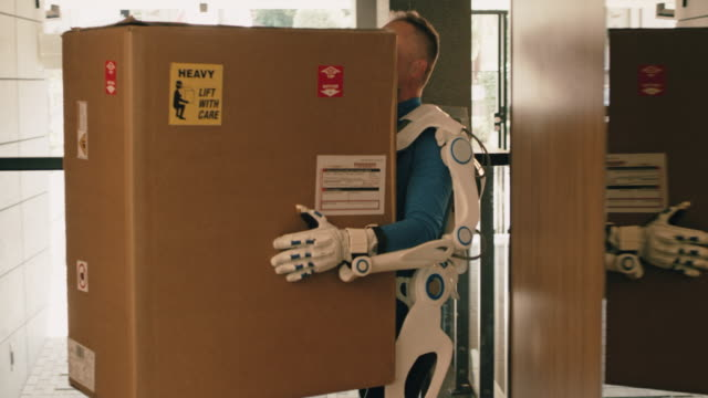 proffesional home mover in exoskeleton. furnishing new flat - exoskeleton stock videos & royalty-free footage