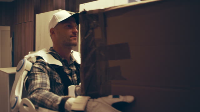 proffesional mover in exoskeleton. carrying heavy boxes up the stairs - removal man stock videos & royalty-free footage