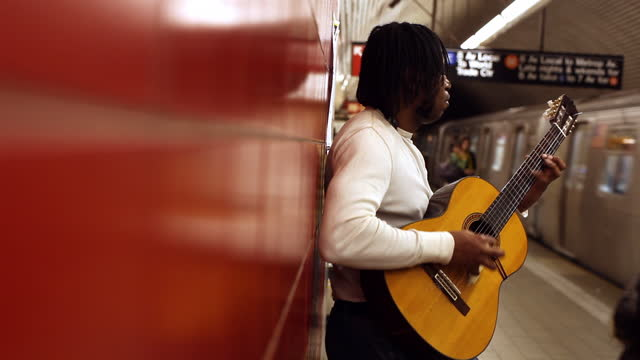 MED profile black man leans against red wall playing guitar in subway station   train leaves   people walk by