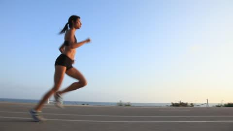 stockvideo's en b-roll-footage met ms pov ts profile male runner running on beach bikepath / los angeles, california, united states - athleticism