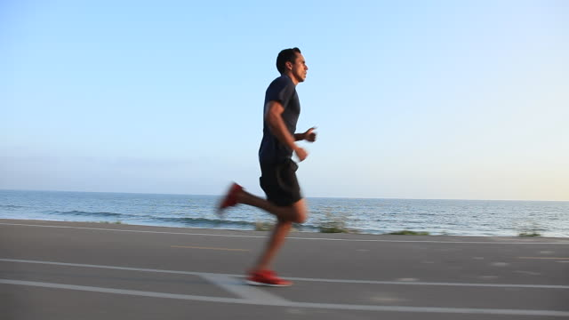 vídeos de stock e filmes b-roll de ms pov ts profile male runner running on beach bikepath / los angeles, california, united states - corredor objeto manufaturado