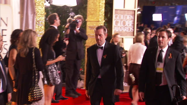 profile MCU Hugh Laurie smiles as he walks quickly down the red carpet