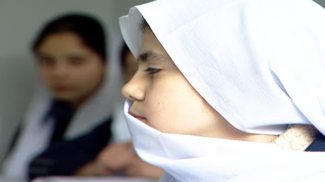 vídeos de stock e filmes b-roll de profile of a druze schoolgirl wearing a traditional headscarf or mandil, attending an english class at irfan, a druze religious school in the chouf... - professora