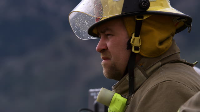 Profile of a firefighter talking to a co-worker at a fire scene