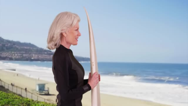 profile of attractive senior woman holding surfboard looking at ocean wave - old diving suit stock videos and b-roll footage