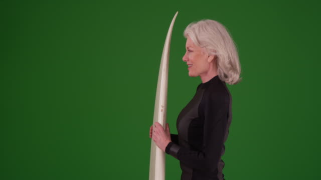 profile of attractive senior woman holding surfboard on greenscreen - old diving suit stock videos and b-roll footage