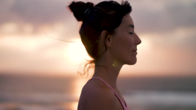 Profile of beautiful mid adult woman practicing yoga on the beach at sunset at Atlantic ocean in the south of France.