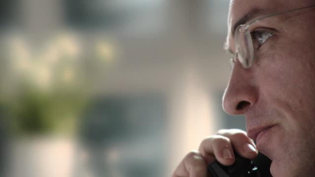 ecu, selective focus, profile of businessman talking on landline phone, berlin, germany - profile stock videos & royalty-free footage