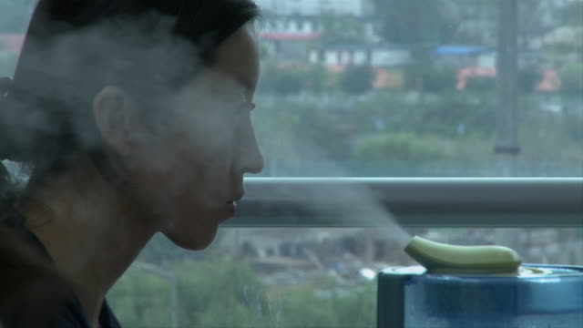 CU Profile of female office worker staring at computer screen, humidifier spraying steam into air in foreground, Beijing, China