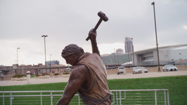 Profile of foundry laborer holding a hammer overhead, working with raw material on an anvil and in the background Omaha cityscape; detail from the bronze statue tilted 'Labor' by Matthew Placeck.