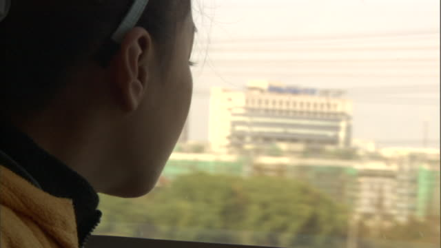vídeos de stock e filmes b-roll de cu profile of girl looking through window of moving maglev train, shanghai, china - perfil vista lateral