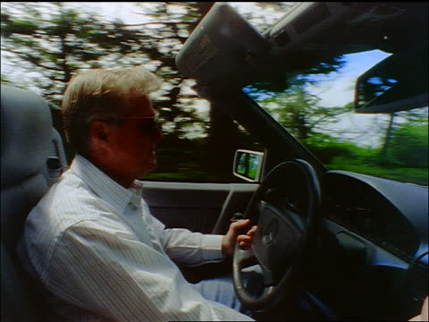 profile of grey-haired man driving convertible on tree-lined road - one mature man only stock-videos und b-roll-filmmaterial