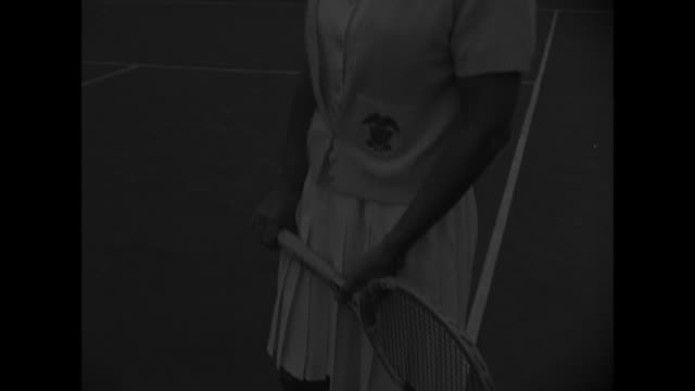 MCU profile of Helen Wills tennis player on tennis court fence buildings in background TILT down to tennis racket in her hands / MCU low angle front...