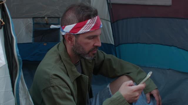 cu profile of homeless man using his smart phone sitting in his sidewalk tent - beggar stock videos & royalty-free footage