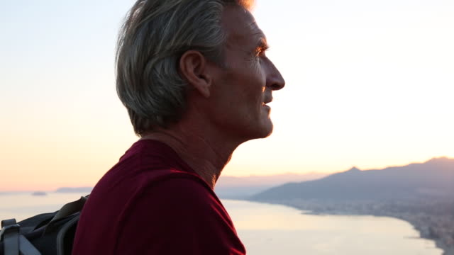 profile of male hiker at sunrise above distant town, sea - ein mann allein stock-videos und b-roll-filmmaterial