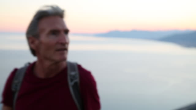 Profile of male hiker at sunrise above distant town, sea