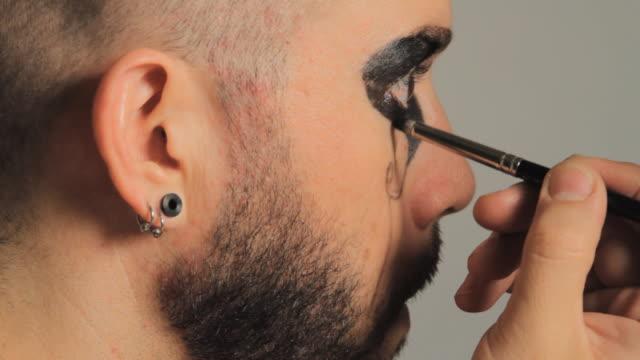 vídeos de stock e filmes b-roll de cu profile of man applying stage make-up around his eye / miami, florida, usa - só um homem maduro