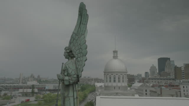 Profile of NotreDamedeBonSecours Chapel rooftop green stone angle statue Bonsecours Market silver dome city buildings skyscrapers BG