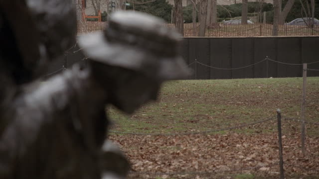 R/F Profile of one of the figures of the Vietnam Women's Memorial statue with the Vietnam Veterans Memorial Wall beyond / Washington, D.C., United States