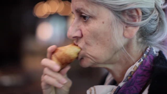 CU SELECTIVE FOCUS Profile of senior woman eating croissant / Estaing, France