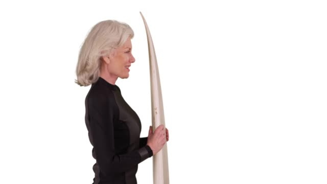 profile of senior woman in wetsuit holding surfboard in studio with copyspace - old diving suit stock videos and b-roll footage