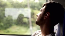 Profile of the handsome dark haired man thoughtfully looking at the window. Travels by train. Looking at camera. Excited about journey. Smiling. Side view
