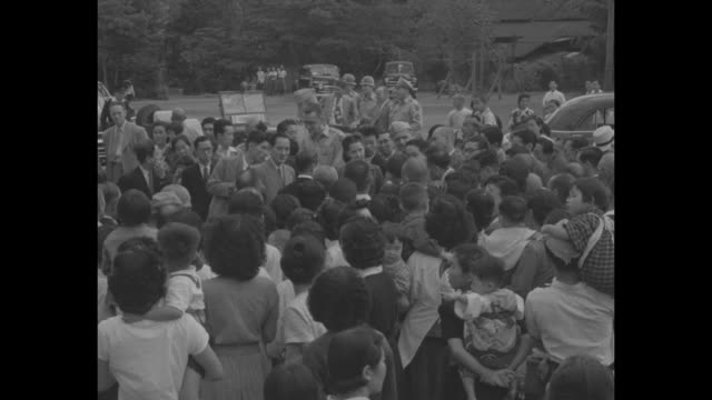 CU profile of US Gen Matthew B Ridgway and wife Penny in village of Nanao Japan / teenage Japanese girls exhibiting sewing / WS villagers gathered...